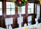 <p>Stół weselny z wysoką dekoracją kwiatową</p>